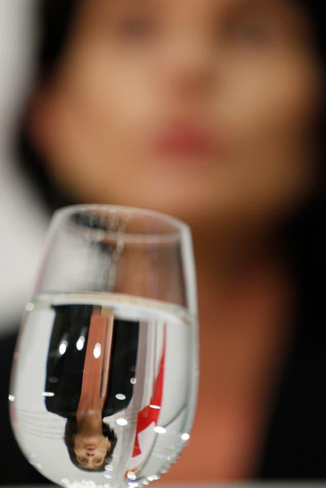 Doris Leuthard, kopfüber gespielgelt in einem vollen Wasserglas.