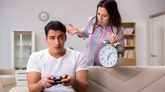 Ein Mann sitzt auf dem Sofa und spielt ein Konsolen-Game, eine Frau erinnert ihn mit einem überdimensionierten Wecker daran, wie viel Zeit er damit schon verbracht hat.