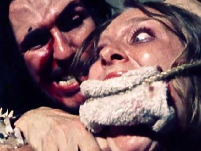 Ein Mann hält einer Frau ein Messer an den Hals.