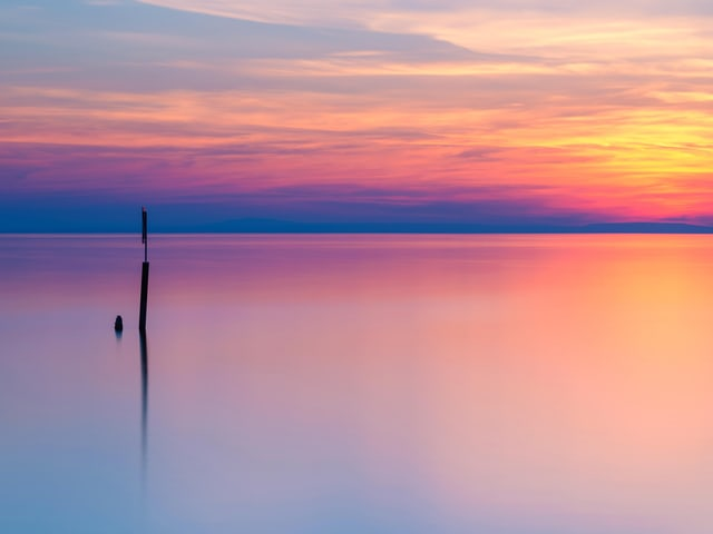 Farbiger Himmel in der Dämmerung mit glatten See im Vordergrund