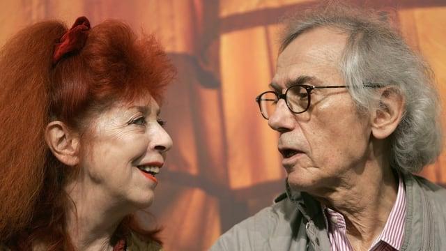 Eine rothaarige Frau und ein weisshaariger Mann blicken sich an.