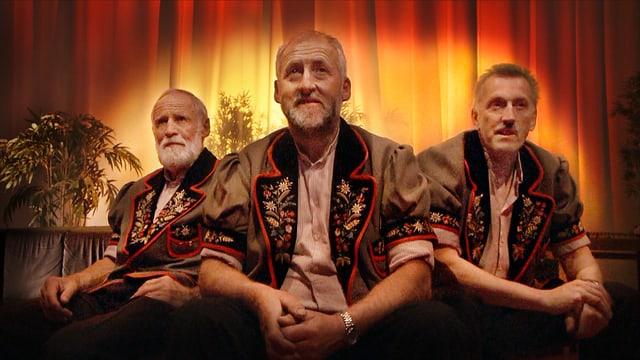 Dre Männer sitzend in traditioneller Schweizer Kleidung.