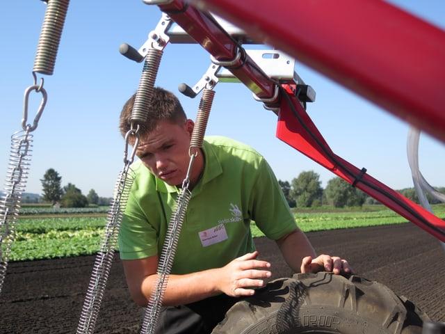 Junger Gemüsegärtner mit Traktor.