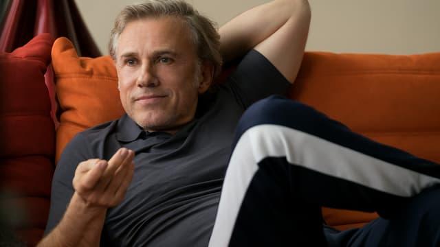 Ein Mann in Trainerhose und T-Shirt sitzt entspannt auf einem Sofa.