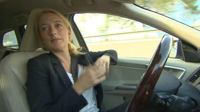 EIne Frau sitzt am Steuer eines fahrenden Autos, die Hände aber nicht auf dem Steuerrad.