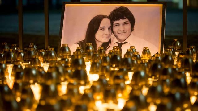 Porträt zweier Personen vor einem Kerzenmeer.