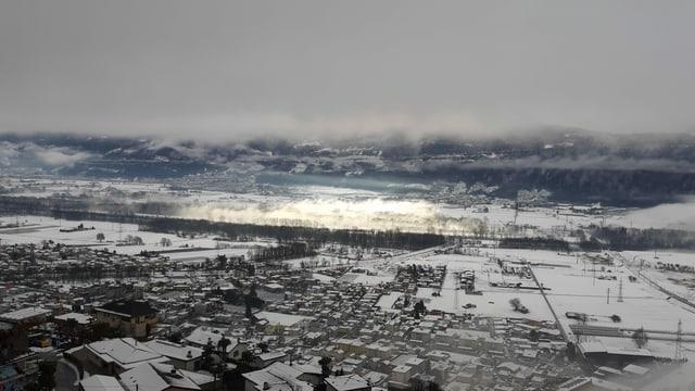 Blick auf die verschneite Magadinoebene mit einem einzigen sonnigen Fleck.