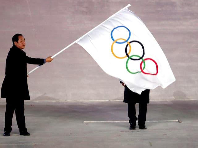 Ein Koreaner schwenkt die Flagge mit den olympischen Ringen.