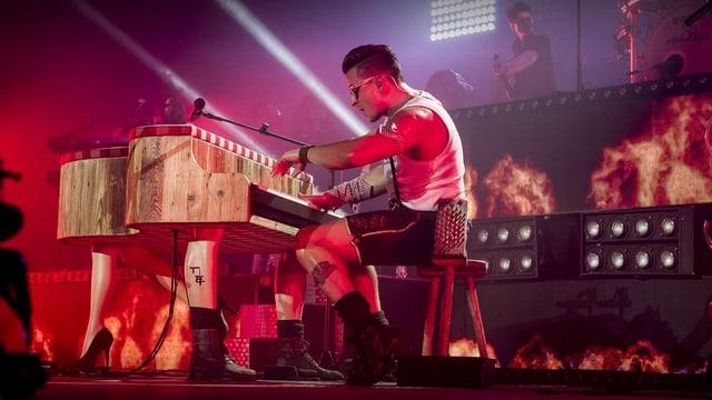 Ein Mann in T-Shirt und Lederhosen am Klavier.