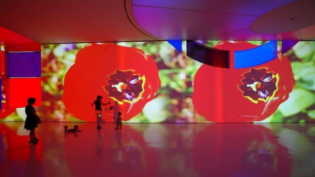 Grosser Raum, an dessn Wände Blumen projiziert werden,