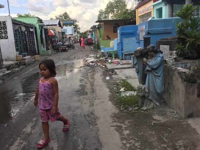 Ein kleines Mädchen überquert die regennasse Strasse, die von Mausoleen gesäumt ist. Im Hintergrund eine Engelsskulptur, die grösser als das Mädchen ist.