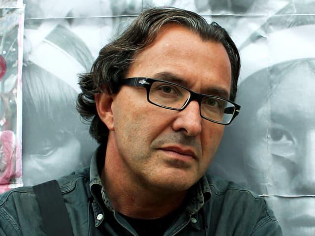 Ein Mann mit Brille und halblangem, gewelltem Haar lehnt an eine Mauer. Er ist braungebrannt.