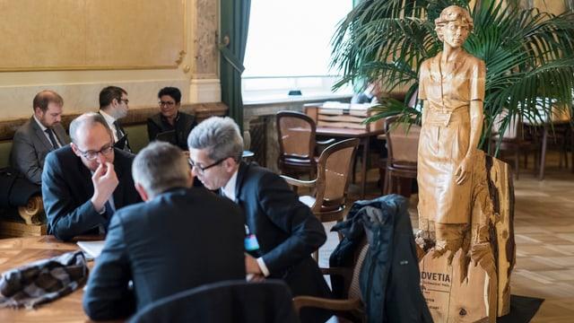 Männer in Anzügen sitzen an Tischen in der Lobby des Bundeshauses und sprechen miteinander.
