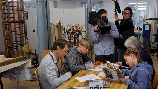 Familie mit zwei Kindern sitzt am Tisch, füllt Fragebogen aus. Kamerateam im Hintergrund.