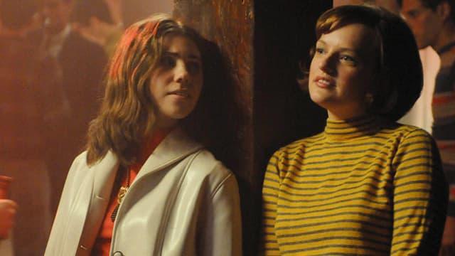 Peggy Olson (Elisabeth Moss) und Joyce (Zosia Mamet) in einem Partylokal.