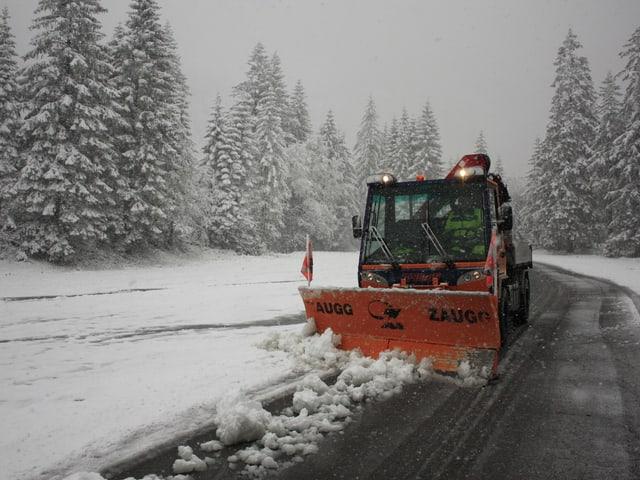 Ein Schneepflug räumt die Strasse frei.