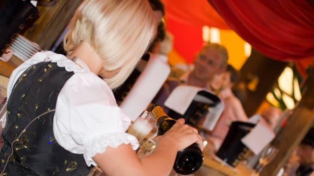 Eine Kellnerin schenkt Champagner ein.