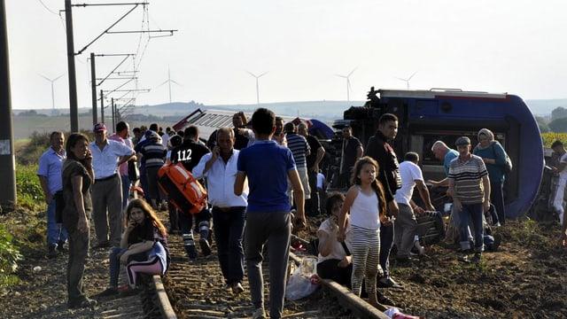 Zahlreiche Menschen neben umgestürzten Waggons.