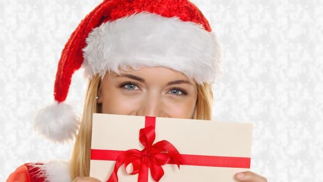 Eine Frau mit Weihnachtsmann-Mütze hält sich einen Geschenkgutschein vors Gesicht.