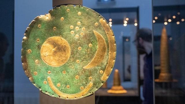 Türkisfarbene Scheibe mit goldener Sonne, Mond und Sternen in einer Vitrine