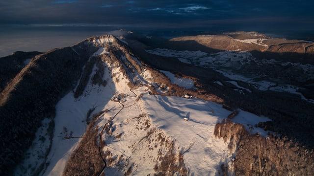 Aus der Vogelperspektive erkennt man den verschneiten Weissenstein im Bild.
