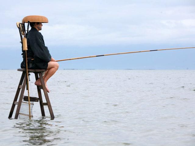 Ein Mann sitzt auf einem hohen Holzstuhl mitten im Wasser und hält eine lange Fischerrute.