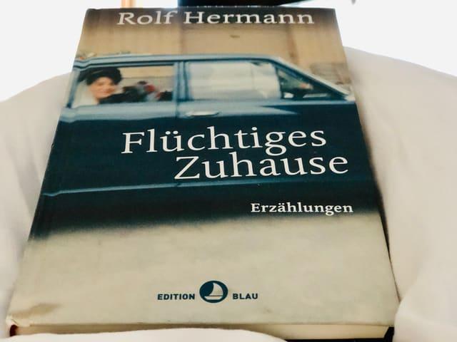 Das Buch  «Flüchtiges Zuhause» von Rolf Hermann liegt auf einer weissen Bettdecke