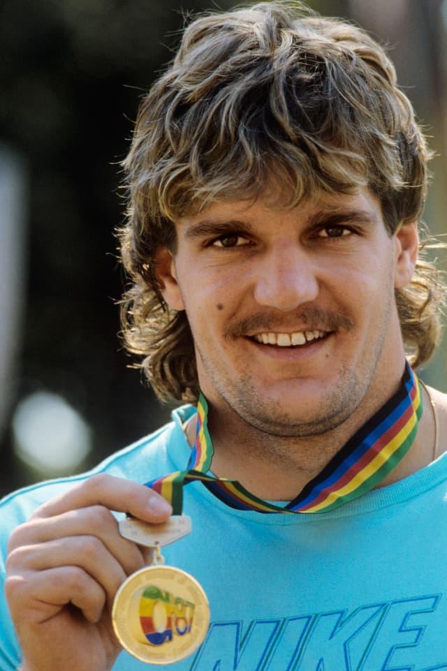 Werner Günthör streckt seine Goldmedaille, die um den Hals hängt, in die Kamera.