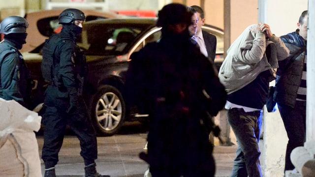 Einer der Festgenommenen wird schwer bewacht in Haft genommen.