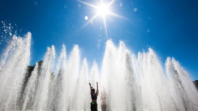 Person in der Sonne in einem Springbrunnen.