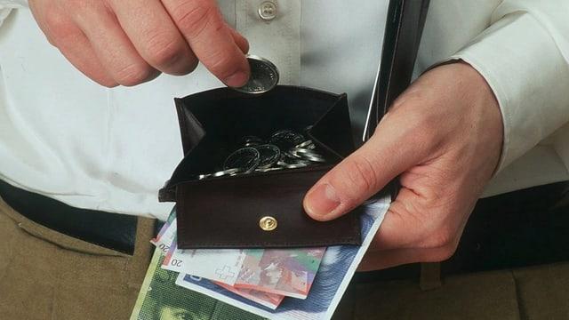 Ein Mann legt eine Münze in sein Portemonnaie, in der Hand hält er Banknoten