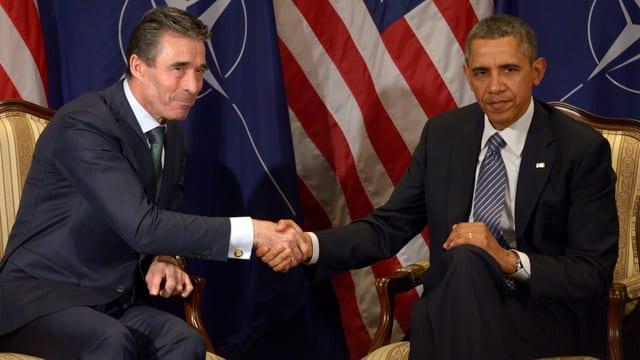 Nato-Chef Rasmussen und Obama geben sich vor Nato- und US-Flagge die Hand.