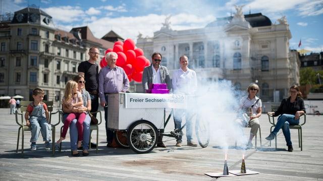 Gruppe von Leuten auf grossem Stadtplatz, davor zwei Feuerwerksvulkane mit Rauch
