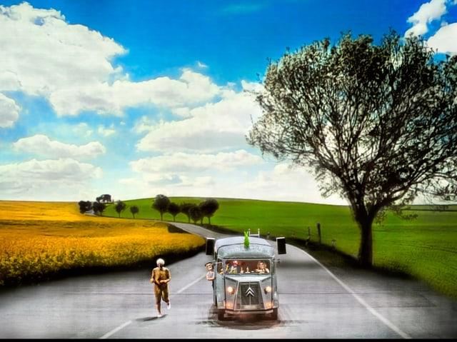 Man sieht ein Auto auf einer Landstrasse. Das Auto selbst ist auf der Bühne, der Rest ist eine Projektion auf die Wand.