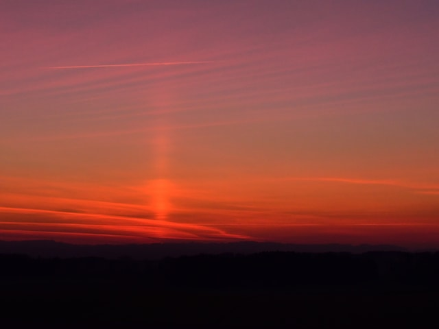 Roter Himmel mit vertikaler Lichtsäule.