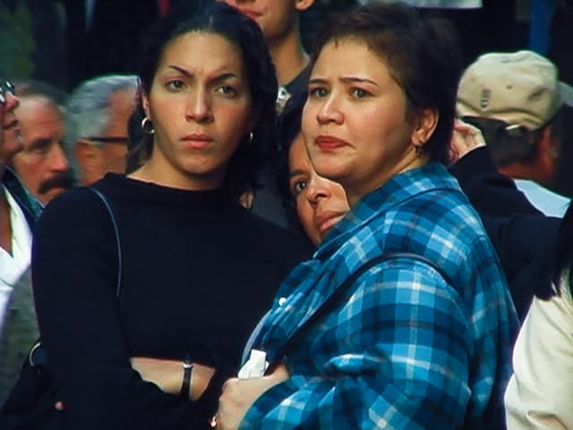 Drei Frauen, die mit versteinerten Gesichtern nach vorne schauen.
