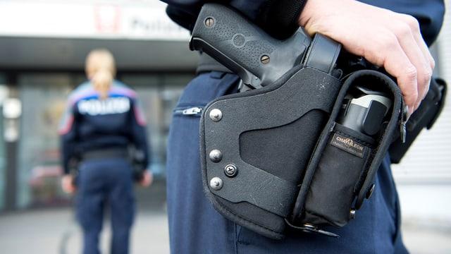 Blick auf die Dienstwaffe am Gürtel eines Polizisten.