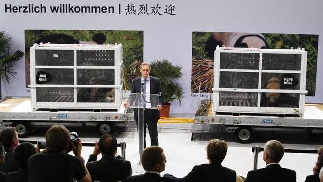 Müller spricht vor den Medien. Hinter ihm stehen die beiden Transportboxen, in denen die Pandas zu sehen sind.