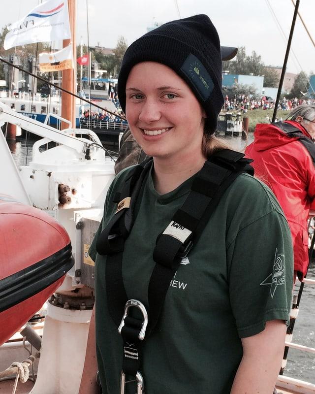 Kathrin Ahlering, gekleidet mit Schiffs-T-Shirt, Mütze und Sicherheitsgurt.