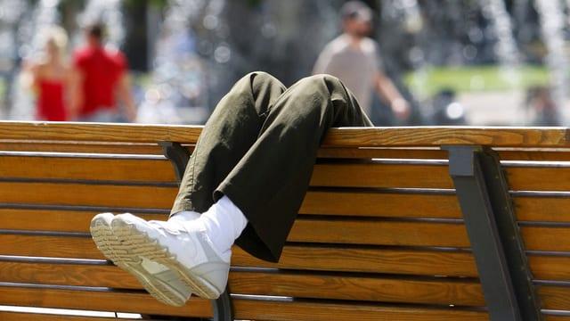 Symbolbild: Beine hängen über eine Parkbank.