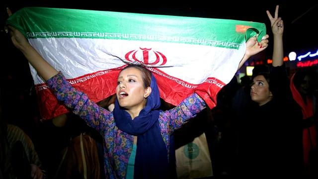 Eine Frau hält die iranische Flagge hoch und ruft etwas in die Menge.