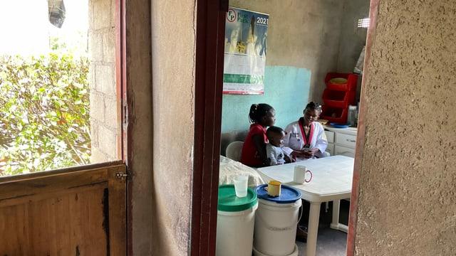 Blick durch Tür in Küche, wo zwei Mädchen und ein Baby am Tisch sitzen