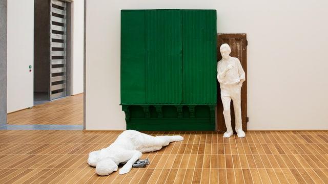 Zwei Figuren aus Gips; die eine lehnt an einen Schrank, die andere liget am Boden.