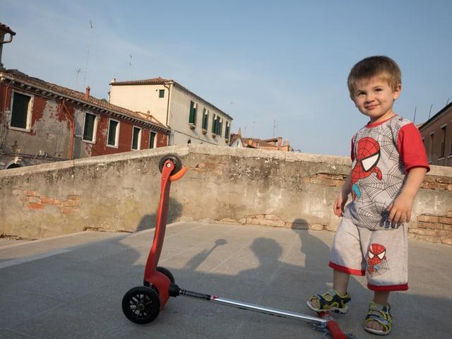 Ein junge mit Trotinett auf einer Brücke.