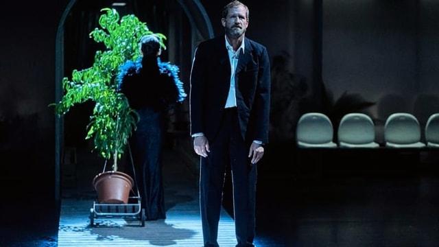 Ein Mann steht niedergeschlagen auf der Bühne.