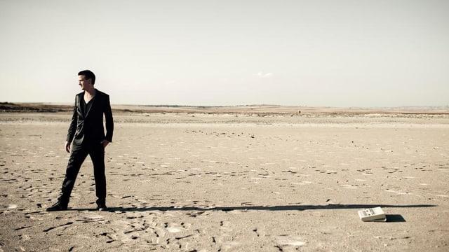 Mann schwarz gekleidet, steht alleine in der Wüste