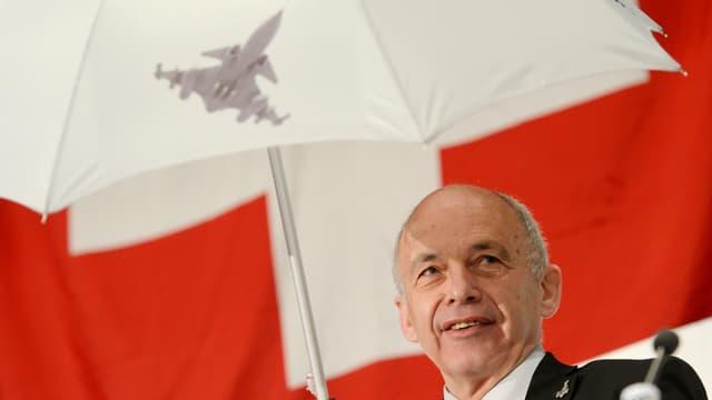 Ueli Maurer unter einem Regenschirm mit Gripen-Bild.