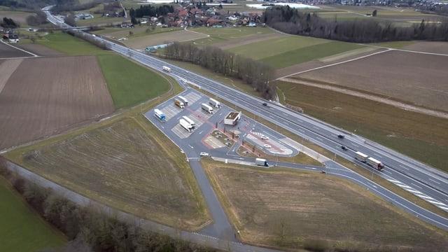 Blick auf das Gelände aus der Vogelperspektive: Autobahnraststätte und daneben Felder.