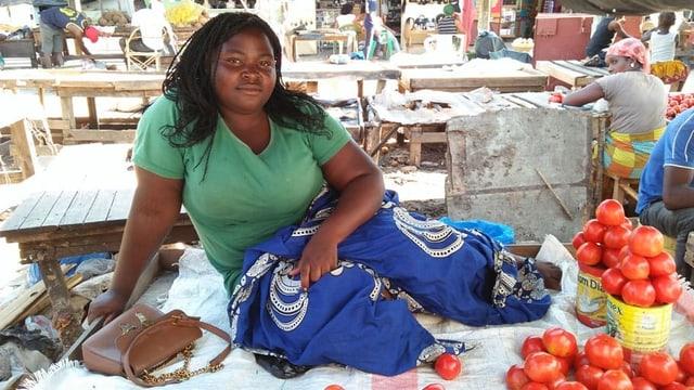 Eine Frau an einem Marktstand mit Tomaten