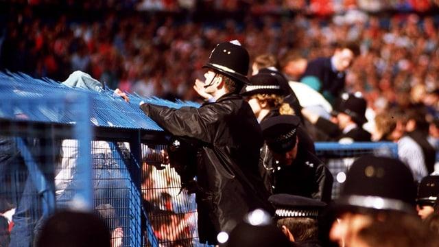 Polizisten stehen am 15. April 1989 im Hillsborough-Stadion an einem Zaun.